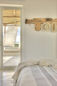 Holiday feeling in bright bedroom with view of veranda curtains blowing in sea breeze