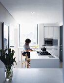 Light-flooded, modern kitchen with gas hob and vintage kettle; woman sitting reading at kitchen counter