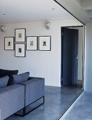 View from balcony of open, blue wooden door, living room couch in same colour and collection of pen and ink drawings on wall