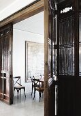 Delicate wooden chairs in dining room with large painting on wall; antique, Chinese wooden partition with large double doors in foreground