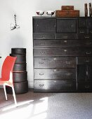 Antique, black chest of drawers next to stacked hatboxes against white wall