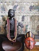 Necklaces hanging on African wooden figurine on polished wooden ornament and wooden mask in front of Chinese picture on wall