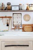 Küchenspüle vor aufgehängten Küchenutensilien mit vielen Gefäßen auf Küchenboard