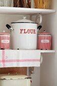 Emailletopf und Emailledosen mit roter Beschriftung auf Küchenboard im Vintagestil