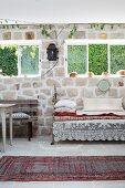 Traditioneller Teppichläufer auf Boden vor Vintage Tagesbett mit Kissen unter Fenster an Natursteinwand