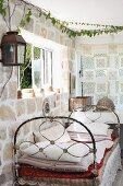 Vintage Tagesbett an Natursteinwand unter Fenster in Zimmerecke eines ländlichen Wohnraumes