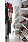 Offenes Regal mit Damenschuhen neben Standspiegel und Kleiderständer in moderner Ankleide