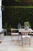 Rostende, filigrane Metallstühle um Tisch mit Marmorplatte auf Terrasse vor hoher Heckenwand