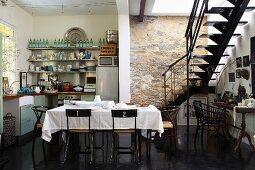 Küche mit unverputzter Steinmauer, Innentreppe, Kochnische und Esstisch