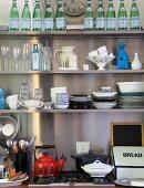 Wandregal mit Geschirr, Gläsern, Dekogegenständen und Wasserflaschen über dem Küchenherd