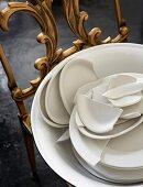 Zerbrochenes Geschirr in einer Schüssel auf antikem Stuhl