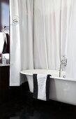 Badezimmer in Schwarzweiss mit Badewanne und Duschvorhang