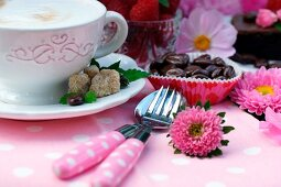 Cappuccinotasse neben Dessertbesteck und Kaffeebohnen in Papiermanschetten auf dekoriertem Gartentisch