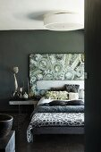 Scatter cushions and bedspreads on double bed in front of modern painting on dark grey wall