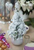 Miniature Christmas tree with artificial snow as centrepiece on set table