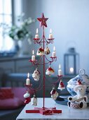 Stylised, red metal Christmas tree with lit candles and toys on table
