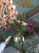 Silver bird figurines clipped to branches below lit chandelier
