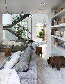 Blick zwischen Sofalandschaft und Einbauregal auf filigrane Wohnraumtreppe und die offene Haustür mit traditionellem Rundbogen