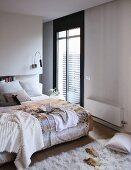 Doppelbett mit Plüschtextilien und Rückwand mit eingebautem Bücherregal