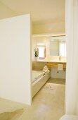 Blick auf durchgehende Waschtischplatte mit Holzschubladen und seitliche Einbauwanne in schlichtes Bad Ensuite