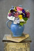 Romantic bouquet in a pitcher on a vintage stool