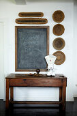 Blackboard for shopping lists and wooden bowls decorating wall above retro kitchen scales on old, rustic table