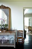 Orchids and gilt-framed mirror on old wooden table next to doorway with view into living room with traditional upholstered armchairs