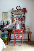 Girlish collection of soft toys, hats and bags on rustic wooden table with pink-painted wooden chair