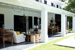 Comfortable sofa in seating area and dining table below wrought iron pendant lamps on terrace with masonry pergola