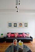 Glass coffee table opposite black leather couch against wall below Warhol screen prints in minimalist interior