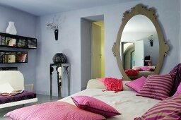 Liege mit violett gestreiften Kissen, Ovalspiegel in hellblau getöntem Wohnraum
