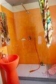Designerbad mit orangefarbenen Wänden im Duschbereich und orangefarbenem Standwaschbecken