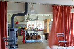 Converted farmhouse kitchen with sink unit and free-standing log burner separated from living room by wafting curtain