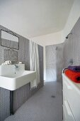 Ensuite bathroom clad in grey mosaic tiles with open shower and industrial-style sink