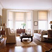 Living room: elegant, light colored furniture with a bay window and half-closed Roman blinds at the windows