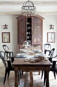 Gedecke auf antikem Tisch und Stühle im Retrostil vor Bauernschrank in ländlich elegantem Esszimmer