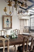 Antique wooden chairs around wooden table below multiple-armed candle chandelier in elegant, rustic dining room