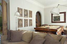 Couch vor Stehleuchten und Billardtisch in traditionellem Gesellschaftszimmer