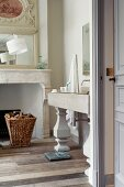 Washstand with column-style legs next to open fireplace in traditional, elegant bathroom