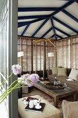Blick in offenen Wintergarten mit gemütlicher Sofagarnitur vor Fenster und geschlossener Jalousie