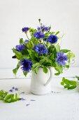 Posy of cornflowers and sweet pea tendrils in jug