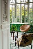 Two comfortable chairs and table in classic conservatory with green wall tiles and mosaic floor