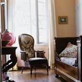 Armchair next to daybed in Southern French interior furnished in historical style