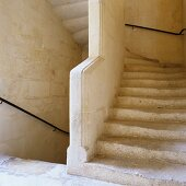 Looking up an historic stone staircase with simple, wrought iron handrails