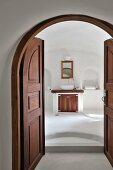 Open double doors of dark wood in arched doorway and view into minimalist bathroom with washstand flanked by niches