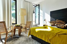 Mustard yellow bedspread on double bed with black headboard next to rustic table and chairs