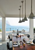 Stylish place settings on table on roofed terrace with sea view