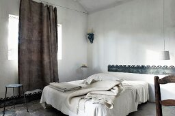 Various blankets on French bed, casual linen curtain hung from taut wire and sheet metal bands as borders on wall