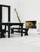 High contrasts in the living room with an antique style, black, lacquer dining table on a while tile floor. open brick fireplace and tree trunk sculpture in the corner