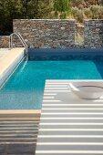 Pool mit Natursteinmauer in mediterraner Landschaft; Licht- und Schattenspiel auf einem Tisch